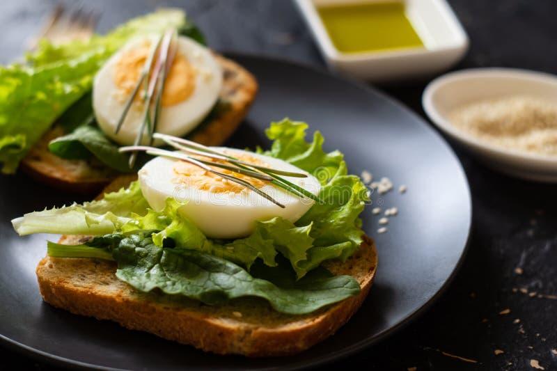 Tueste del pan ?cimo con la lechuga, albahaca, huevo y microgreen imagenes de archivo