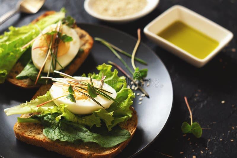 Tueste del pan ?cimo con la lechuga, albahaca, huevo y microgreen fotos de archivo