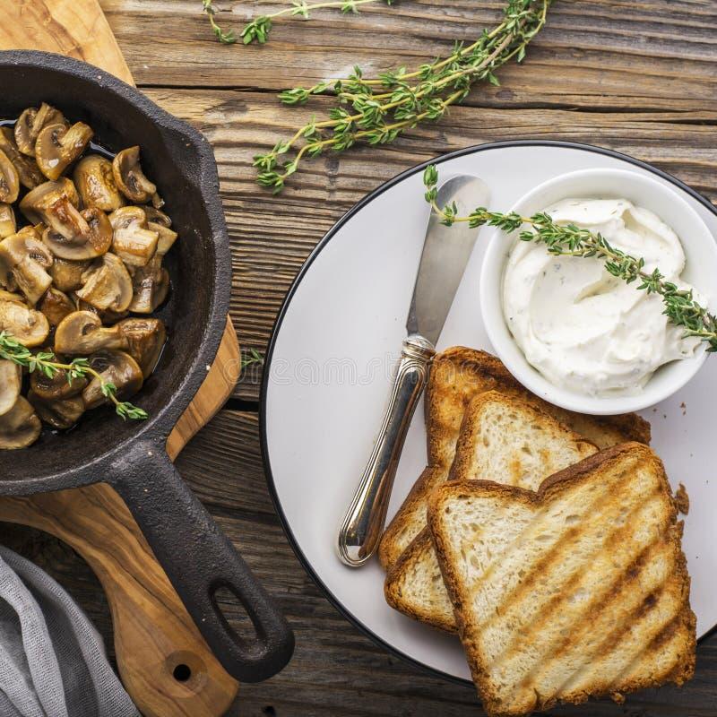 Tueste el desayuno asado a la parrilla pan con queso cuajado y setas fritas encendido Visión superior fotografía de archivo