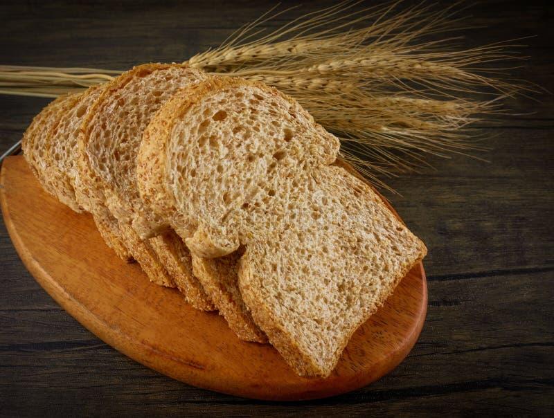 Tueste los panes en la placa de madera y la tabla de madera imagenes de archivo