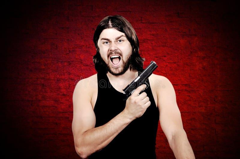 Tueur avec l'arme à feu photographie stock
