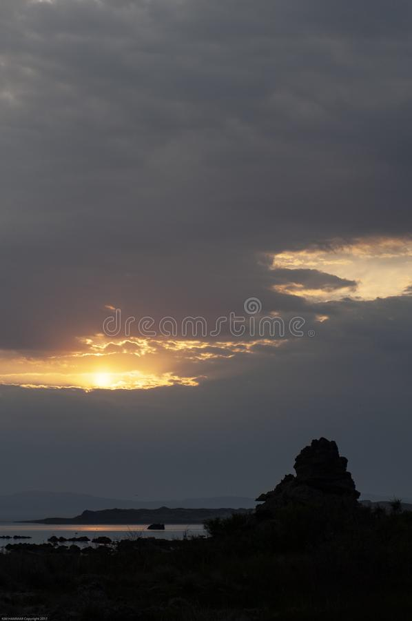 A morning sunrise peaks through heavy clouds to reveal a silhouette of a tufa at Mono Lake. royalty free stock photography