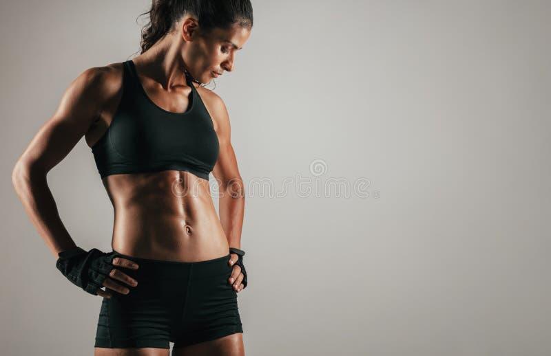 Tuff kvinna med åtsittande buk- muskler arkivbild