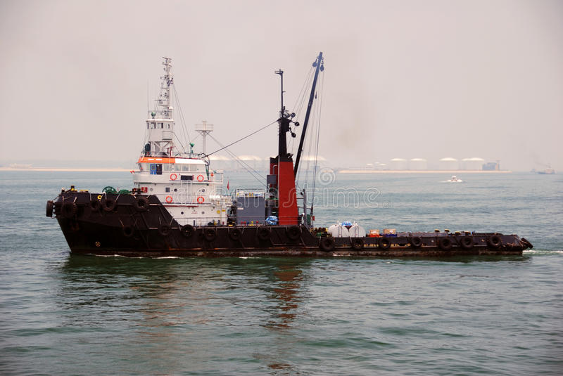 Tug and barge in Singapore anchorage. royalty free stock photography