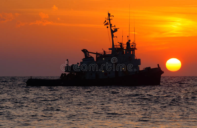 Tug boat. Orange sunset over water with the silhouette of a tug boat stock photo