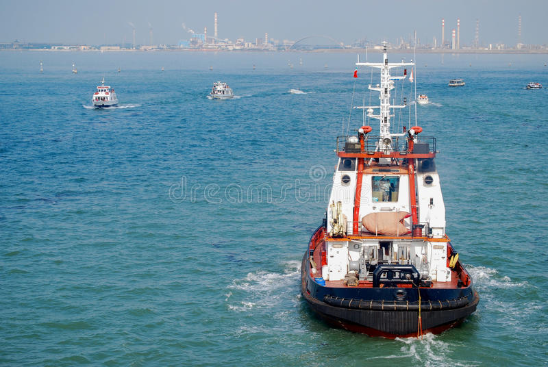 Tug boat in Grand Canal of Venice. Under hazy blue sky the tug boats of Venice Grand Canal help to position the large cruise ships into port. Placed the working royalty free stock photo