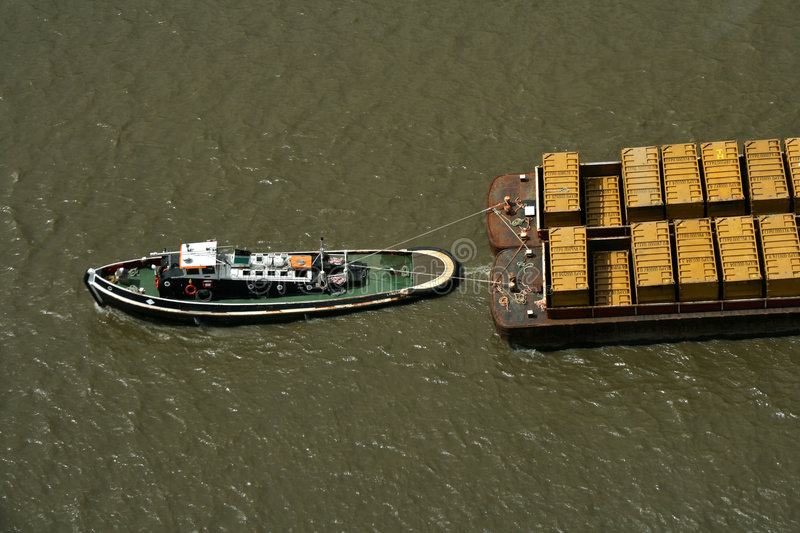 Tug boat pulling refuse containers royalty free stock image