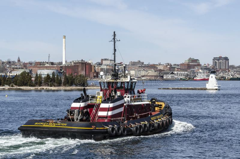 Tug Buckley McAllister  with lighthouse in background. New Bedford, Massachusetts, USA - April 11, 2019: Tug Buckley McAllister crossing New Bedford inner harbor stock photos