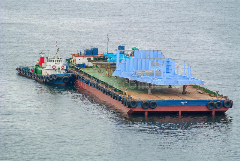 A tug moving a barge with large ship components stock photo