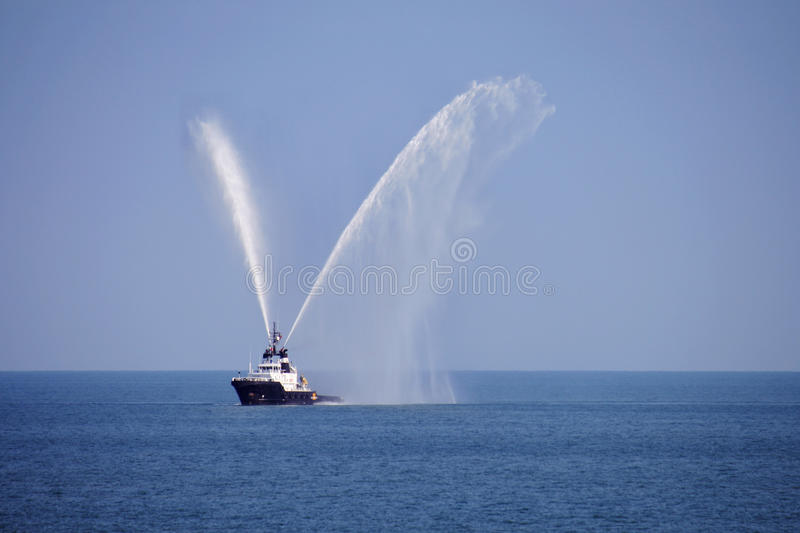 Tug showing fire fighting jets royalty free stock photography