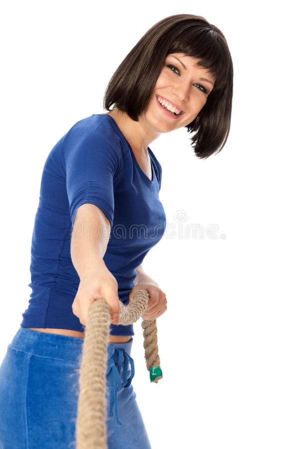 Tug of war. The strong-willed woman plays of pulling of a rope and wins royalty free stock image