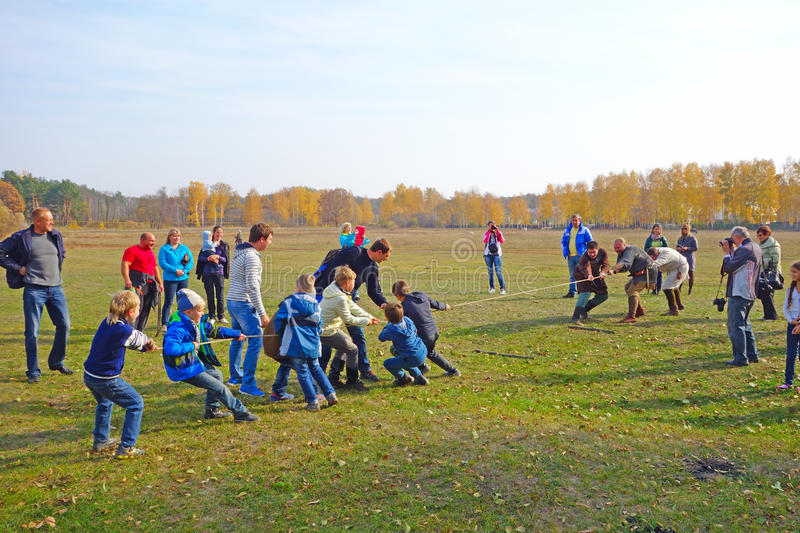 Tug of war - children against adults royalty free stock photo