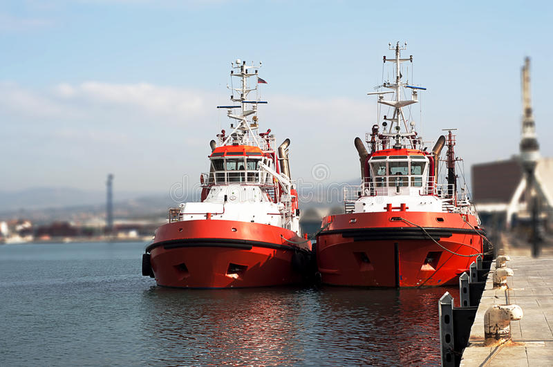 Tugboat. Two powerful red tugboat docked at harbor stock photo