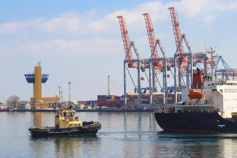 Tugboat assisting Cargo Ship maneuvered into the Port of Odessa, Ukraine. Handling of goods and the work of a commercial port royalty free stock photo