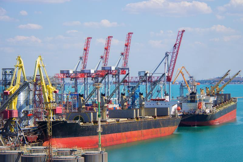 Tugboat assisting container cargo ship to harbor quayside. stock image