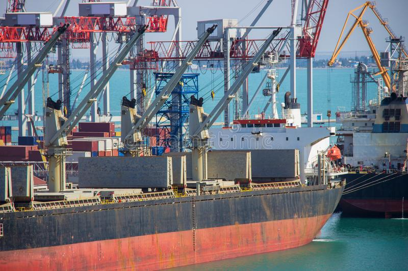 Tugboat assisting container cargo ship to harbor quayside. royalty free stock photography