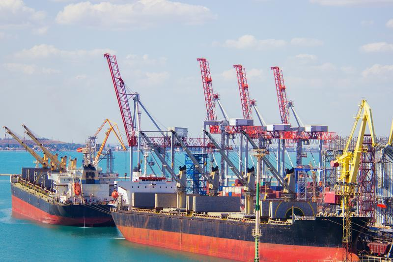 Tugboat assisting container cargo ship to harbor quayside. royalty free stock images