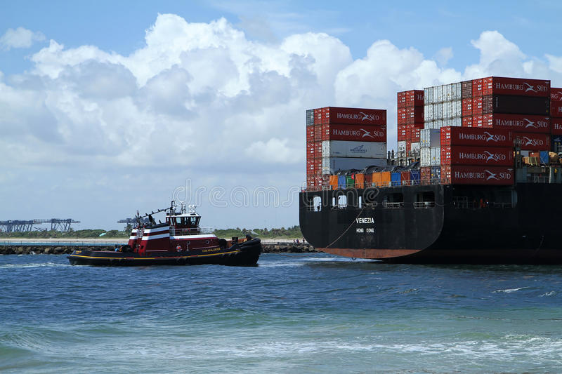 Tugboat assisting container ship Venezia. FORT LAUDERDALE, FL, USA: MAY 28, 2015, container ship Venezia loaded with cargo is assisted into Port Everglades by stock image