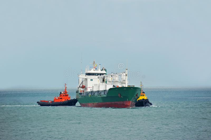 Tugboat assisting refrigerated cargo carrier stock photo