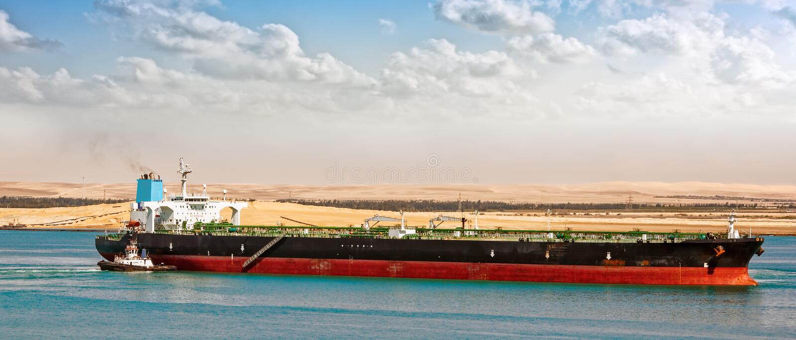 Tugboat assisting supertanker. Tugboat tugs help turn around a large oil tanker. Egypt Suez canal northbound stock images