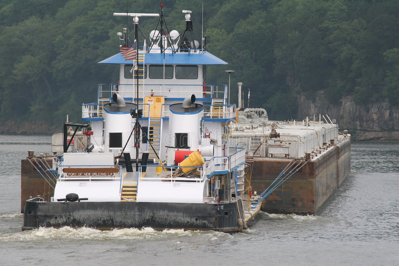 Tugboat and barge. Tugboat pushing barge on river royalty free stock photography