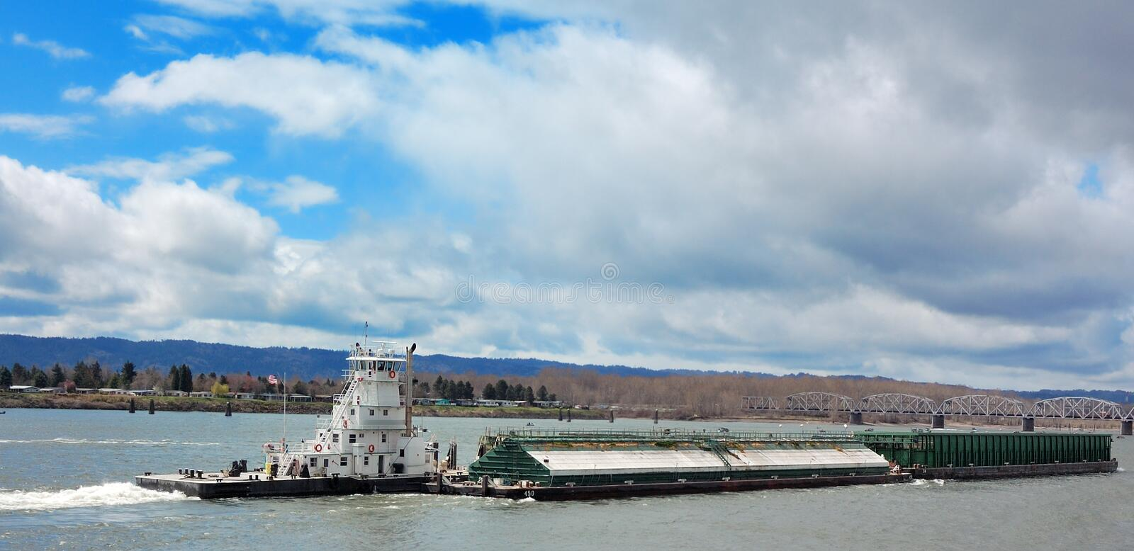 Tugboat and Barge on River. A tugboat pushing a barge under clouds with blue sky peeking through royalty free stock photos