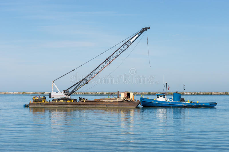 Tugboat And Barge. A small tugboat prepares to shove a barge laden with construction materials and a crane westward inside the breakwall at the Port of Cleveland stock photos
