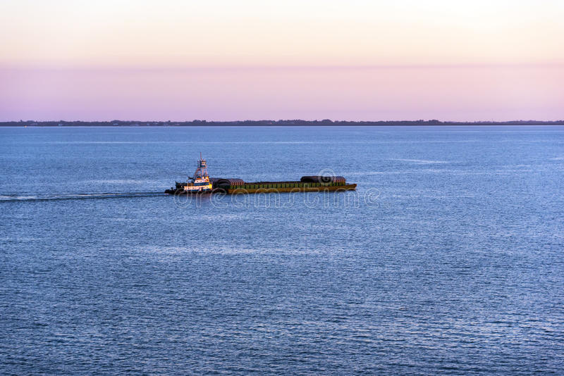 Tugboat and Barge. Tugboat pushing a barge across tampa bay at sunset royalty free stock photo