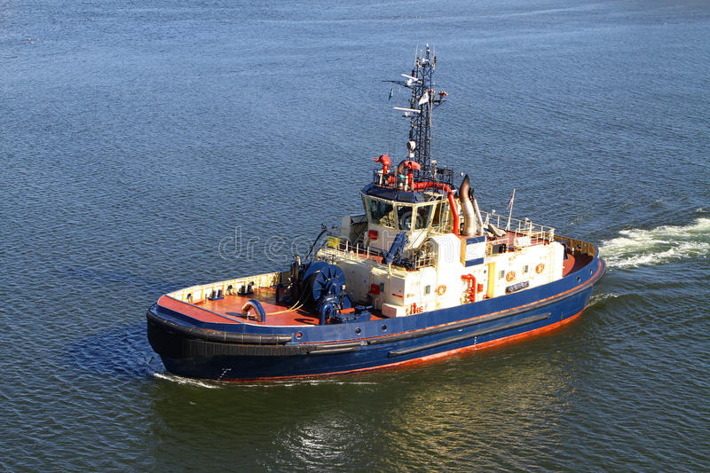 Tugboat. A blue tugboat leaving harbour to assist a large cargo ship royalty free stock photos
