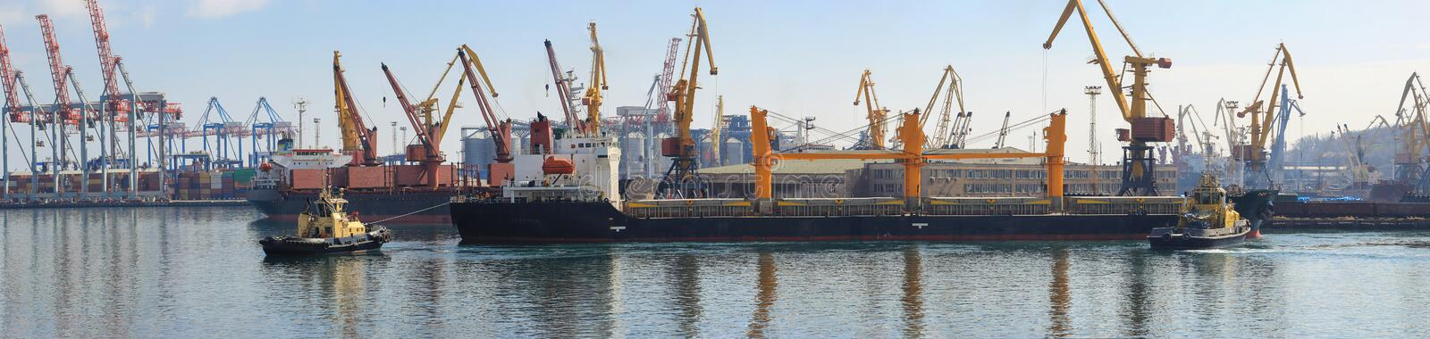 Tugboat at the bow of cargo ship , assisting the vessel to maneuver in Sea Port. Of Odessa. Lifting cargo cranes, ships and grain dryer in  Port stock photo