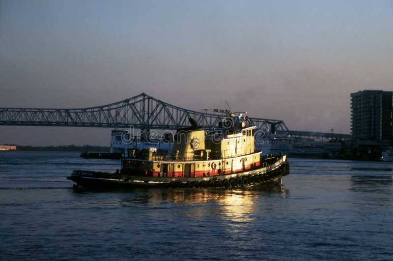 Tugboat and bridge. Tugboat crossing Mississippi river in morning light stock image