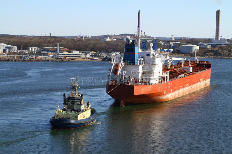 Tugboat with cargo ship. A blue tugboat assisting a large red oil tanker stock photos