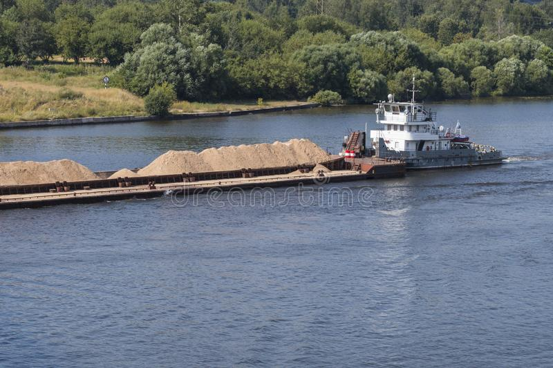 A tugboat carries barge with sand. Along the river stock images