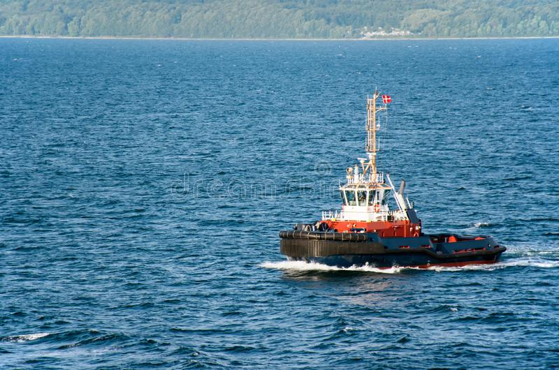 A tugboat with a Danish flag navigates on the sea, in the background the wooded coast can be seen royalty free stock photos