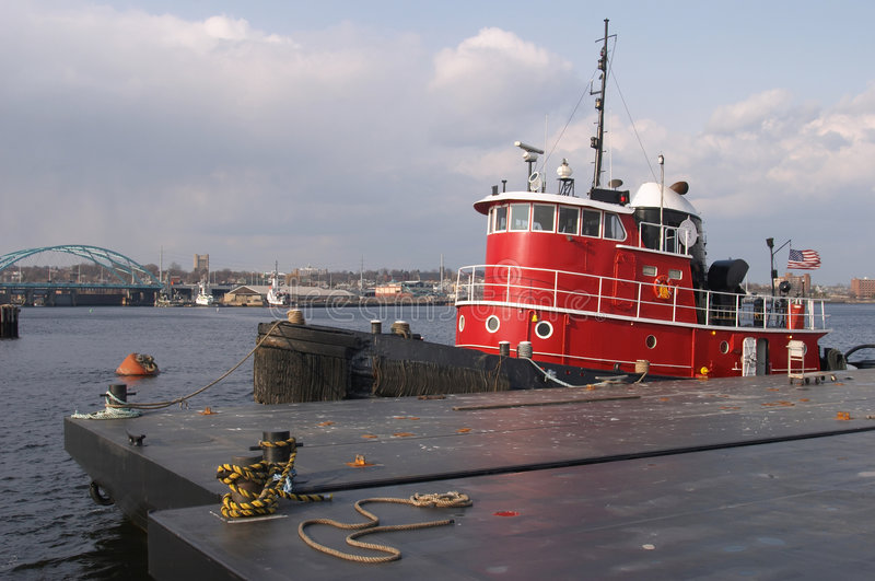 Tugboat at the dock. Red tugboat at the dock in the ocean stock photo