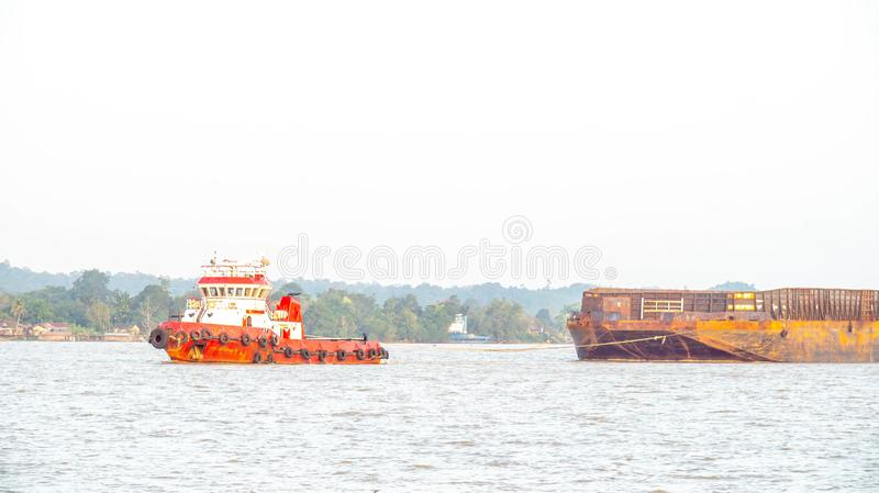 Tugboat dragging empty barge at Mahakam River, Samarinda, Indonesia. Industrial and shipping stock photography