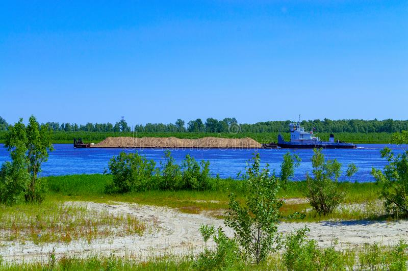 A tugboat floats on a river in Siberia and pushes a barge with sand. Summer. Greenery. Side view stock images