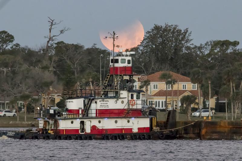 Tugboat under supermoon eclipse stock photography