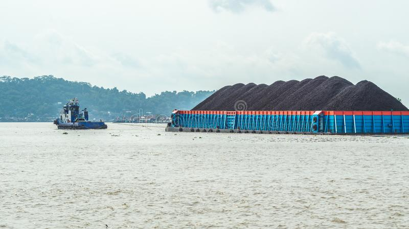 Tugboat and heave loaded barge. A tugboat pull a heavy loaded barge with coal cruising the Mahakam River in Samarinda, Indonesia royalty free stock photography
