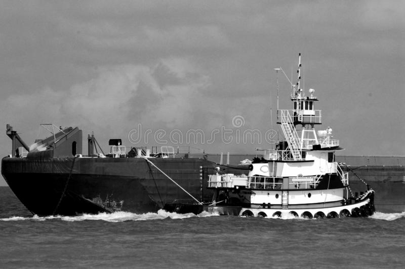 Tugboat moving barge background. Tugboat towing barge at the ocean inlet Florida, USA royalty free stock photo
