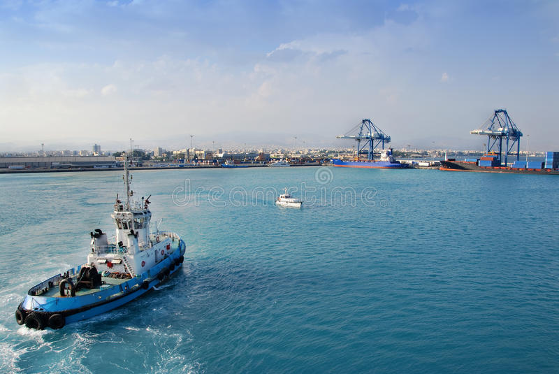 Tugboat nears Container Port, Cyprus. A tugboat in the Mediterranean Sea heads to the container port in Limossal, Cyprus, with containers, cranes and the city in stock photos