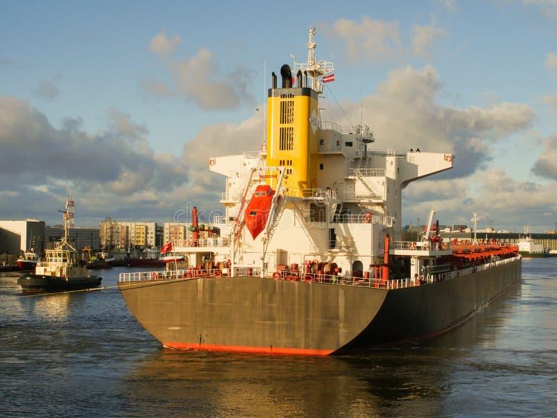 Tugboat pomaga masowego ładunku statek opuszczać port obrazy royalty free