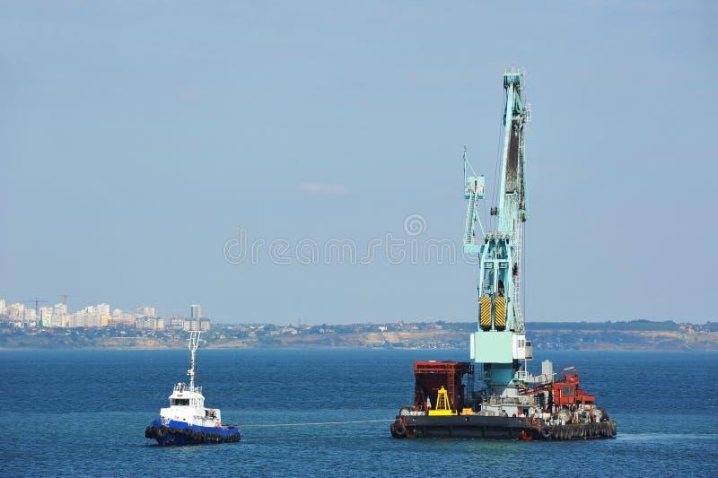 Tugboat pomaga spławowego ładunku żurawia obrazy stock