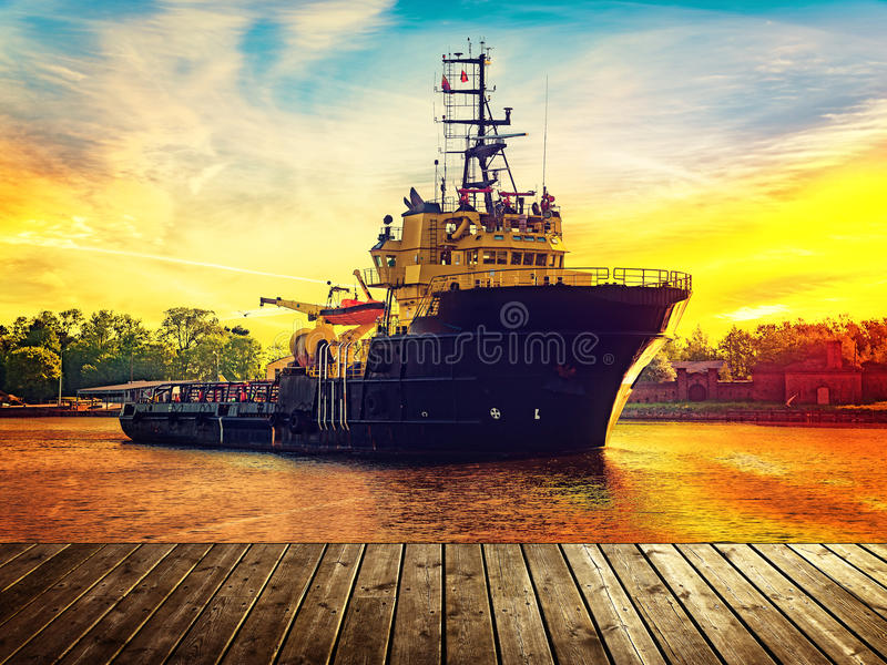 Tugboat in port. View from wooden pier with tugboat in port during sunset stock photos