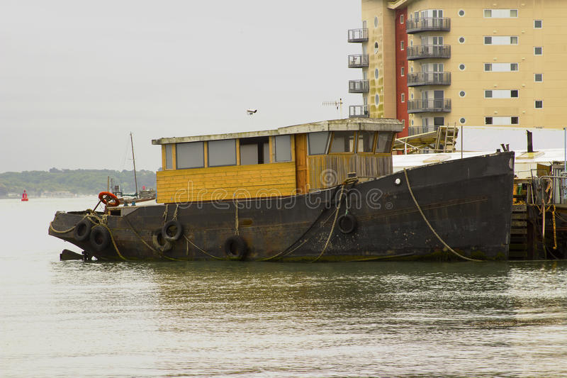 A tugboat in the process of being converted to a pleasure craft tied up at the quayside in Hythe harbour on Southampton Water on t stock image