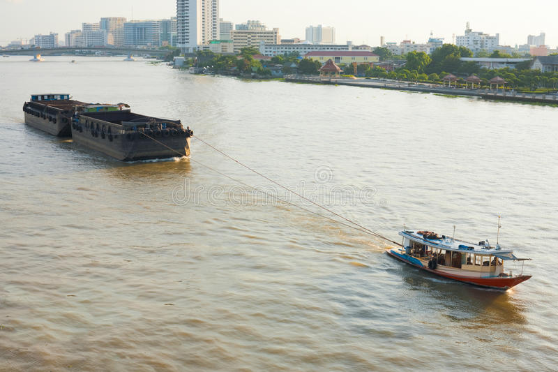 Tugboat Pulling Barge. A small tugboat pulls a large barge up the Chao Phraya River in Bangkok, Thailand royalty free stock photography