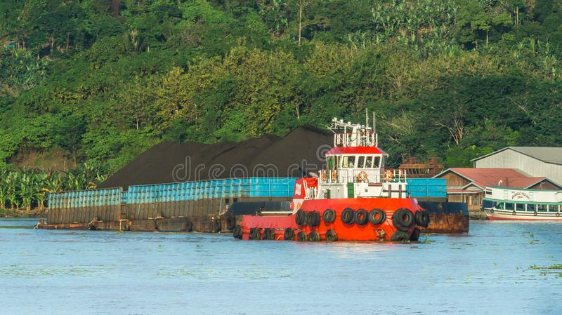 Tugboat pulling barge full of black coal in Mahakam river, Borneo, indonesia. Industry and environment concept royalty free stock photography