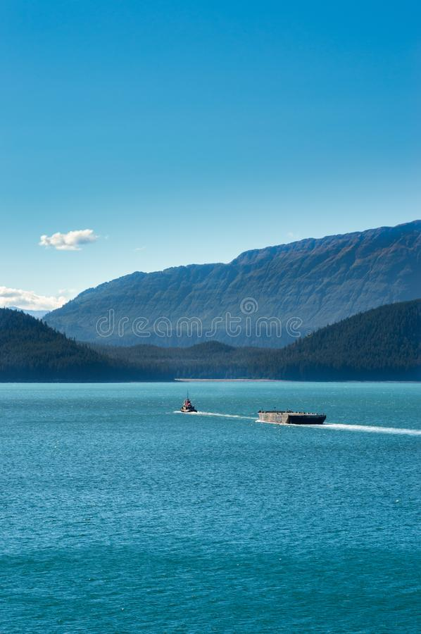 Tugboat pulling barge on a sunny day. Gastineau Channel, Juneau, Alaska, USA. Tugboat pulling barge on a sunny day in Gastineau Channel, near Juneau, Alaska royalty free stock images