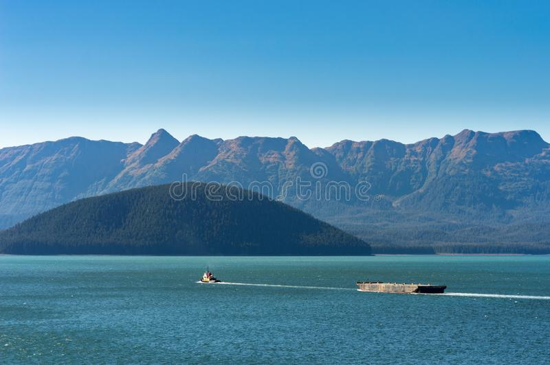 Tugboat pulling barge on a sunny day. Gastineau Channel, Juneau, Alaska, USA. Tugboat pulling barge on a sunny day in Gastineau Channel, near Juneau, Alaska royalty free stock image