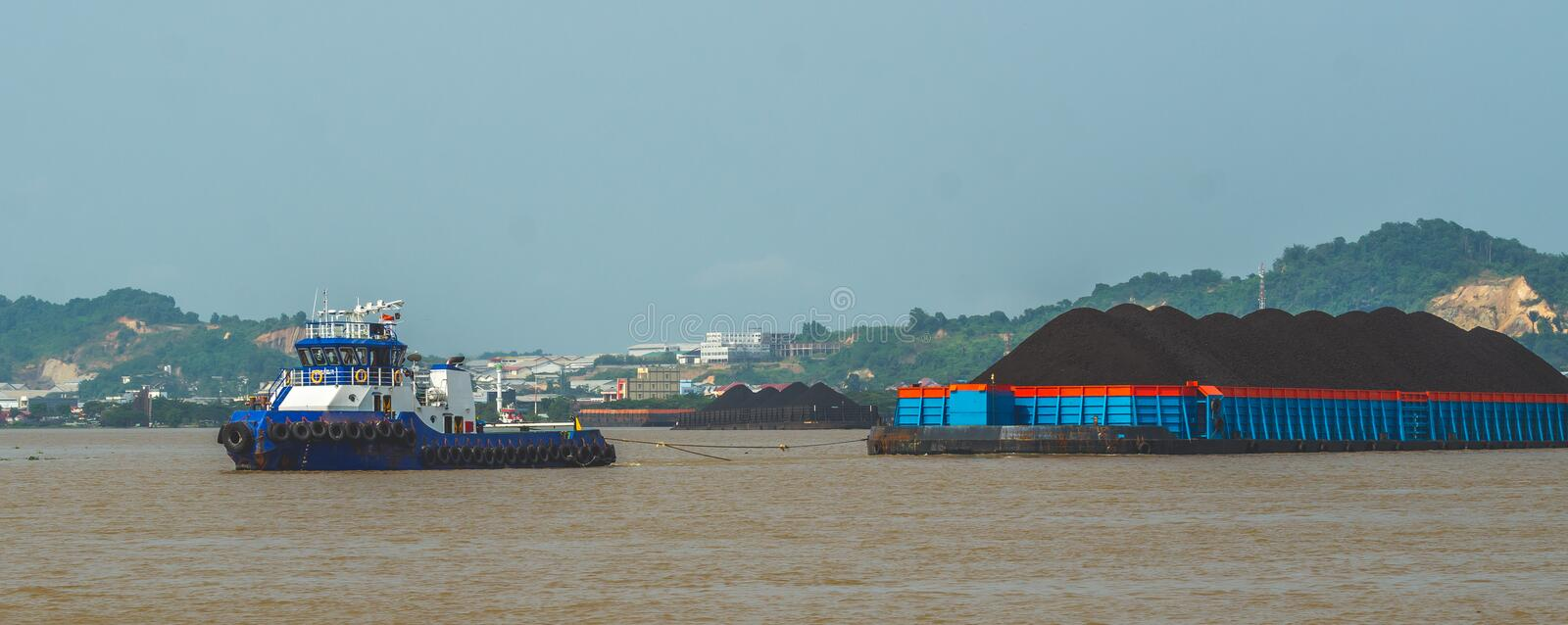 Tugboat pull heavy loaded barge of coal. Tugboat pulling heavy loaded barge of coal cruising Mahakam River, Samarinda, Indonesia royalty free stock photo